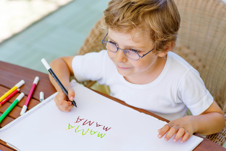 Portrait of cute happy preschool kid boy with glasses at home making homework. Little child writing mama with colorful pencils, indoors. School, education concept