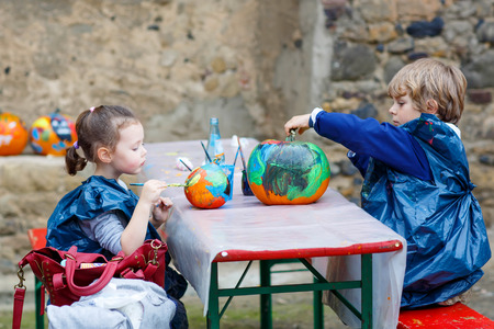Two little kids, boy and girl on a harvest festival, painting with colors a pumpkin. Children celebrating traditional festival halloween or thanksgiving.