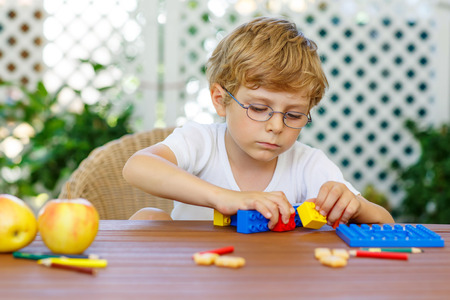 Beautiful blond child with glasses playing with lots of colorful plastic blocks indoor. Active kid boy having fun with building and creating. Archivio Fotografico