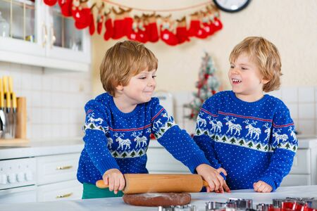 pullovers: Two little kid boys baking gingerbread cookies. Happy siblings, children in blue xmas pullovers. Kitchen decorated for Christmas. Family, holiday, kids lifestyle concept.
