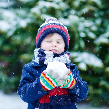 having fun in the snow: Cute little funny child in colorful winter clothes having fun with snow and making ball, outdoors during snowfall on cold day. Active outdoors leisure with children in winter. Stock Photo