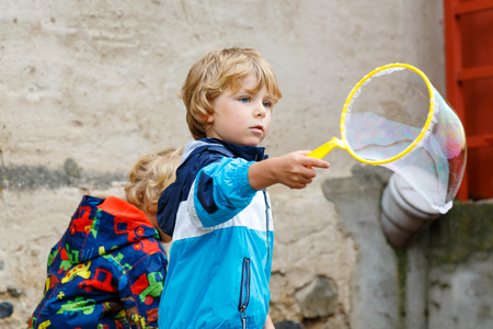 Four years old caucasian child boy blowing soap bubbles outdoor on birthday party - happy carefree childhood. Kid having fun.