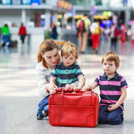 airport: Happy family of three: Mother and two little sibling boys at the airport, traveling together. Stock Photo