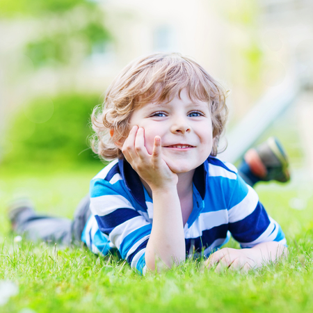 hot boy: Happy child enjoying on grass field and dreaming. Cute blond boy with blue eyes on warm sunny summer day, outdoors.