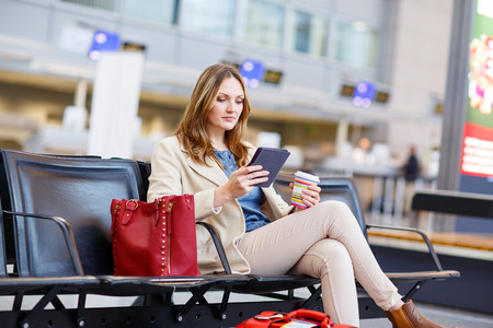 Young woman at international airport, reading her ebook and drinking coffee while waiting for her flight on business trip. Female passenger at terminal, indoors. Stock Photo