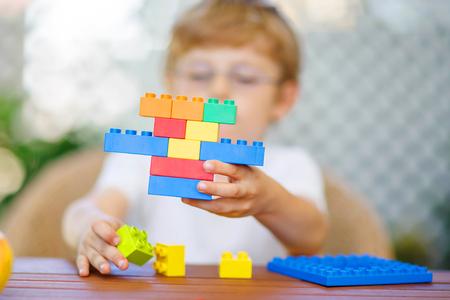 Malé dítě s brýlemi hrát se spoustou barevných plastových bloků vnitřních. kid chlapec zábavu s budovou a tvorby. Selektivní zaměření na hračce Reklamní fotografie
