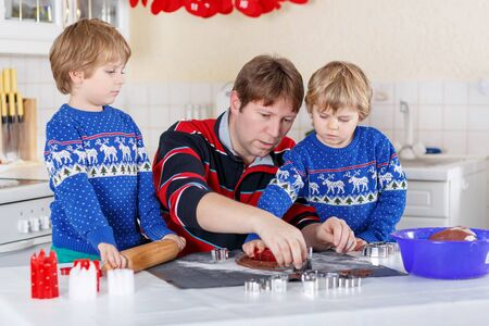 pullovers: Two little kid boys and dad baking gingerbread cookies. Happy siblings, children in blue xmas pullovers. Kitchen decorated for Christmas. Family, holiday, kids lifestyle concept.