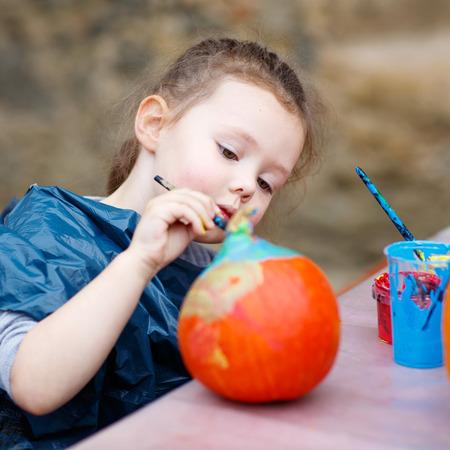 calabaza: Ni�a ni�o feliz en una fiesta de la cosecha, la pintura con los colores de una calabaza. Ni�o celebrando fiesta tradicional de Halloween o acci�n de gracias. Foto de archivo