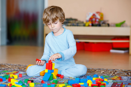 kids toys: Adorable little child playing with lots of colorful wooden blocks indoor. Active kid boy  having fun with building and creating. People, lifestyle, childhood, nursery concept Stock Photo