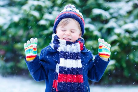 outoors: Happy little funny child in colorful winter clothes having fun with snow, outdoors during snowfall on cold day. Active outoors leisure with children in winter.