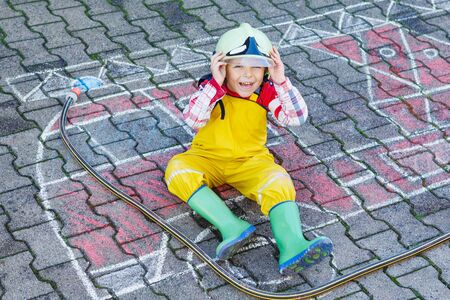 of boy: Creative leisure for kids: cute kid boy in helmet having fun with fire truck picture drawing with chalk, outdoors. Dreaming of future profession.