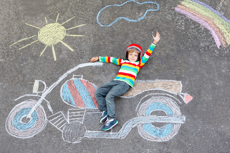 Creative leisure for children: Adorable little child of four years in helmet having fun with motorcycle picture drawing with colorful chalks. Children, lifestyle, fun concept. Stock Photo