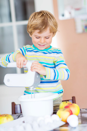 cake mixer: Cute funny blond preschool kid boy baking apple cake in domestic kitchen. Happy child having fun with working with mixer, flour, eggs and fruits.
