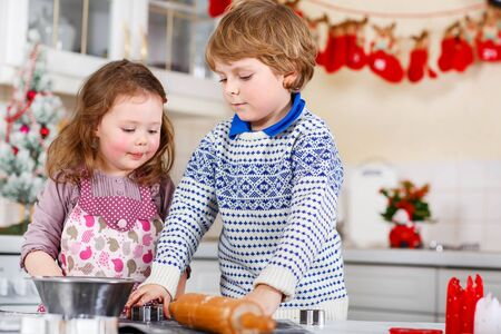 brother sister: Boy and girl baking Christmas cookies at home. Siblings, brother and little sister having fun in domestic decorated kitchen. Traditional leisure with kids on Xmas