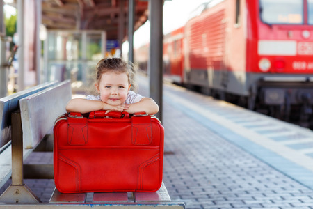 Funny little girl with big red suitcase on a railway station. Kid waiting for train and happy about traveling. Archivio Fotografico