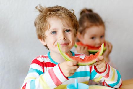 niños en la escuela: Feliz adorable niño y niña comiendo alimentos saludables, sandía fresca en el jardín infantil, guardería o en casa. Las frutas frescas como aperitivo bio orgánica para niños.