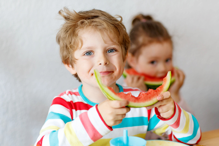 Happy adorable kid boy and little girl eating healthy food, fresh watermelon in kindergarten, nursery or at home. Fresh fruits as organic bio snack for children. Zdjęcie Seryjne
