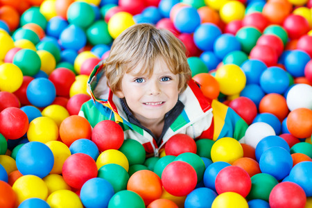 Happy little kid boy playing at colorful plastic balls playground high view. Adorable child having fun indoors. Archivio Fotografico