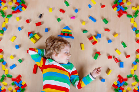 kids learning: Little blond child playing with lots of colorful wooden blocks indoor. Active kid boy wearing colorful shirt and having fun with building and creating. Stock Photo