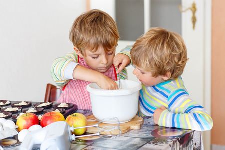 cake mixer: Two happy little blond kid boys, friends baking apple cake in domestic kitchen. Children having fun with working with mixer, eggs and fruits. Tasting dough
