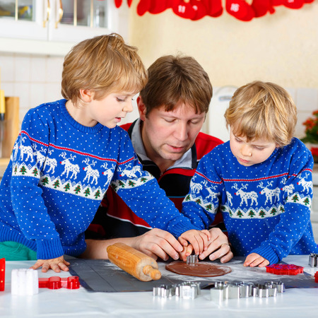 pullovers: Two little siblings and father baking gingerbread cookies. Happy siblings, children in blue xmas pullovers. Kitchen decorated for Christmas. Family, holiday, kids lifestyle conceplt.