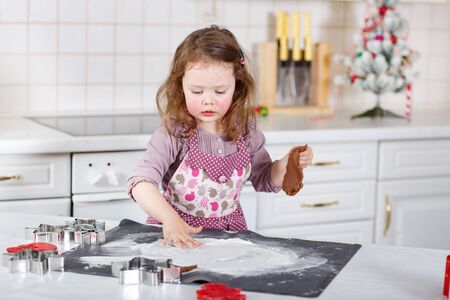 gingerbread cookie: Happy little child, cute kid girl, sitting at the table in domestic kitchen making delicious sweet gingerbread xmas cookies. Kitchen decorated for Christmas Stock Photo