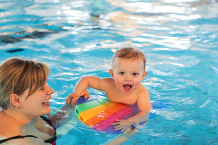 early summer: Happy young mother and little baby swimming in indoor pool. Healthy childhood and growth of children