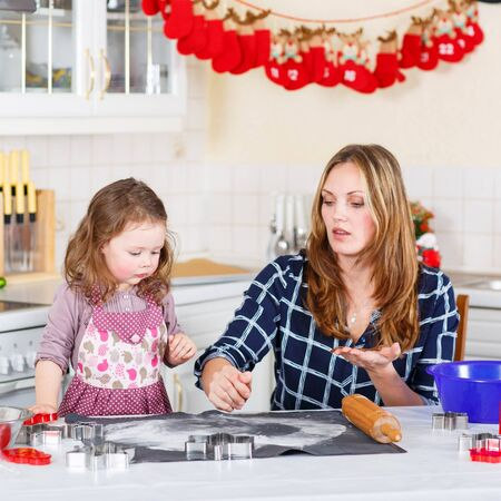 domestic kitchen: Happy mother, young woman in red santa hat baking christmas cookies together with her little daughter, cute blonde kid girl, sitting at the table in domestic kitchen Stock Photo