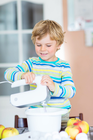 cake mixer: Cute funny blond kid boy of 3 years baking apple cake in domestic kitchen. Happy child having fun with working with mixer, flour, eggs and fruits.