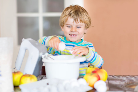 cake mixer: Cute adorable blond kid boy baking apple cake in domestic kitchen. Happy child having fun with working with mixer, flour, eggs and fruits.