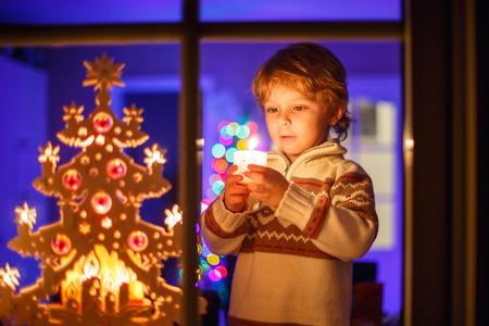 rubia: Adorable ni�o peque�o ni�o, rubio ni�o de pie por la ventana en el tiempo de Navidad y la celebraci�n de vela. Con coloridas luces de �rbol de navidad en el fondo. Vacaciones, estilo de vida, navidad concepto Foto de archivo