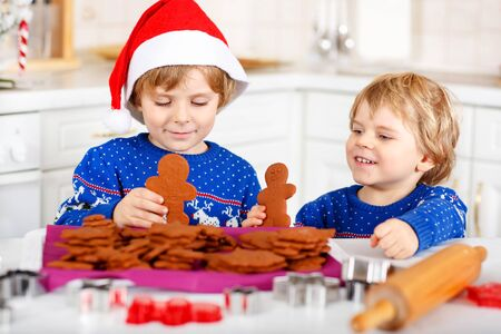 pullovers: Two little kid boys baking gingerbread cookies. Happy siblings, children in blue xmas pullovers. Kitchen decorated for Christmas. Family, holiday, kids lifestyle conceplt. Stock Photo