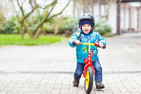 leisure activities: Little kid boy of two years riding with his first bike in the city park. Happy child in colorful clothes. Active leisure for kids outdoors.