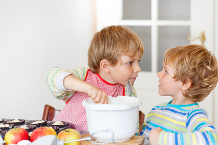 cake mixer: Two little siblings baking apple cake in domestic kitchen. Kid boys having fun with working with mixer, eggs and fruits. Children tasting dough Stock Photo