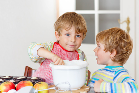 cake mixer: Two little twins, brothers baking apple cake in domestic kitchen. Kid boys having fun with working with mixer, eggs and fruits. Children tasting dough Stock Photo