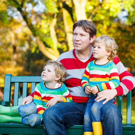 kiddies: Two little kid boys and young father sitting together in colorful clothing. Funny blond siblings and their dad having fun in autumn park on warm day. Happy family of three.