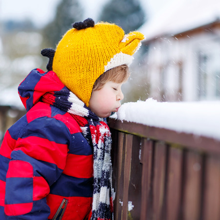 outoors: Little kid boy in colorful clothes happy about snow, blowing on it, outdoors  on cold day. Active outoors leisure with children in winter.
