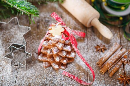 gingerbread cookie: Homemade baked Christmas gingerbread tree on vintage wooden background. Anise, cinnamon, baking roll, star forms and decoration utensils. With icing sugar als snow. Selfmade gift for xmas.