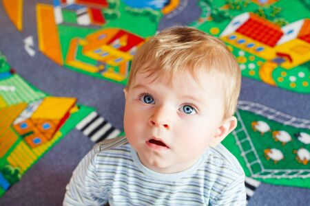 keen: Beautiful little baby boy playing with different toys indoors. Home, nursery or kindergarten. Stock Photo