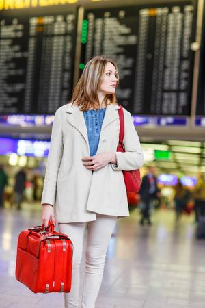 Tired woman at international airport walking through terminal. Upset tourist passenger waiting. Canceled flight due to pilot strike. Stock Photo
