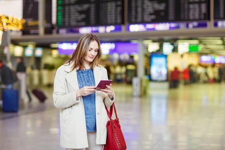 Tired woman at international airport walking through terminal. Upset business passenger waiting. Canceled flight due to pilot strike. Stock Photo