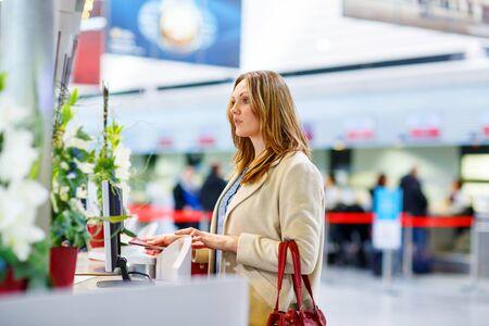 personas enojadas: Mujer cansada en el aeropuerto internacional de la terminal en el escritorio de check-in. Malestar de espera de pasajeros de negocios triste. Cancelado el vuelo debido a huelga de pilotos. Foto de archivo