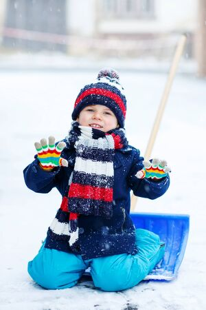 outoors: Cute little beautiful kid boy in colorful winter clothes sitting on snow shovel, outdoors during snowfall on cold day. Active outoors leisure with children in winter.