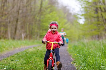 girl sport: Happy funny kid girl and colorful raincoat riding his first bike on summer day. Active leisure for children outdoors.