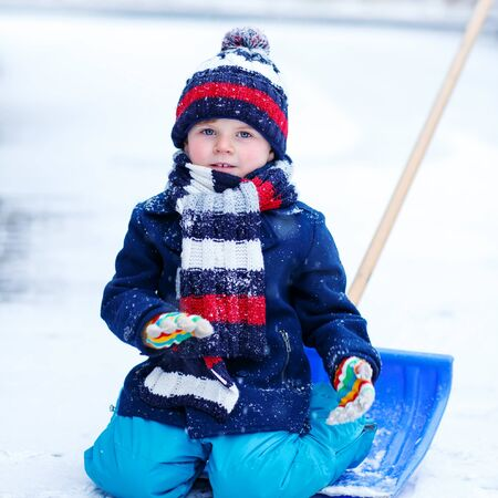 outoors: Little funny toddler in colorful winter clothes sitting on snow shovel, outdoors during snowfall on cold day. Active outoors leisure with children in winter.