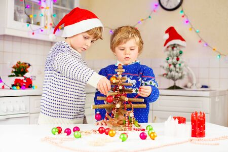 pullovers: Two little kid boys decorating selfmade Christmas tree. Funny twins, children in xmas pullovers. Kitchen decorated for Christmas. Family, holiday, kids lifestyle concept.