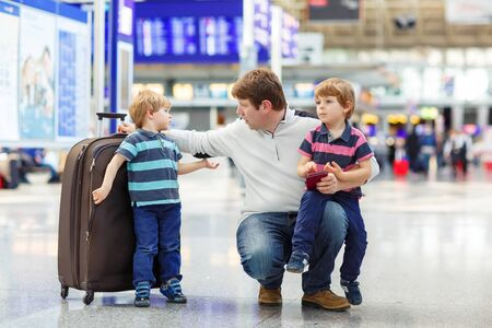 Tired father and two little sibling kids boys at the airport, traveling together. Angry family waiting. Canceled flight due to pilot strike. Stock Photo