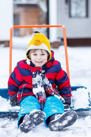 outoors: Happy kid boy having fun with riding on snow shovel , outdoors  on cold day. Active outoors leisure with children in winter.
