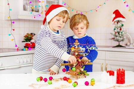 pullovers: Two little kid boys decorating selfmade Christmas tree. Happy siblings, children in xmas pullovers. Kitchen decorated for Christmas. Family, holiday, kids lifestyle concept.