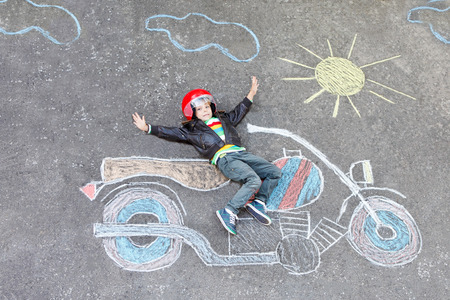 outdoor: Creative leisure for children: Happy little child of four years in helmet having fun with motorcycle picture drawing with colorful chalks. Children, lifestyle, fun concept.
